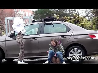 Teen girlfriends pissing behind a parked car