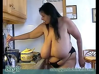 Granny with Giant saggy udders cooks in topless. Massive h. Cow Udders