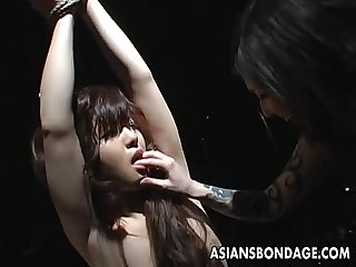 Tied up Asian babe endures some rough nip sucking