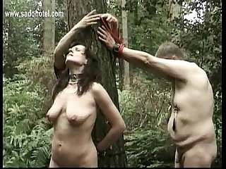 Hot milf slave tied to a tree got pulled on her nipples and got metal clamps with heavy weight on